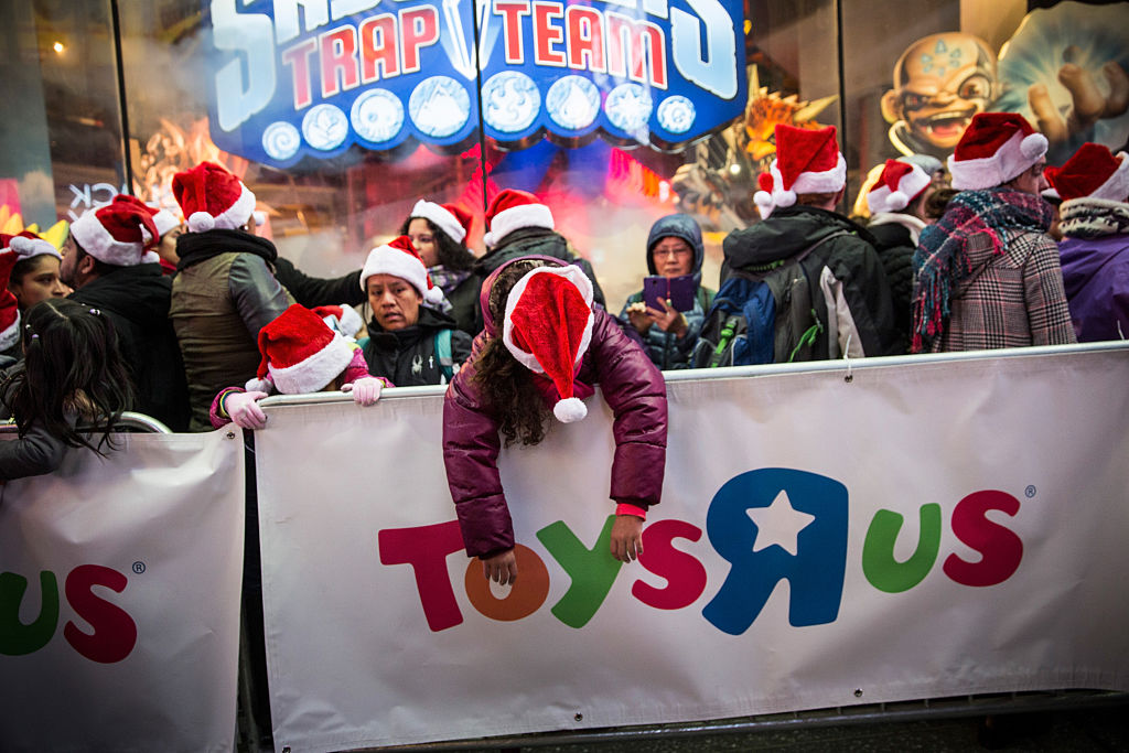 a kid in a santa hat draped over a toys r us sign in times square