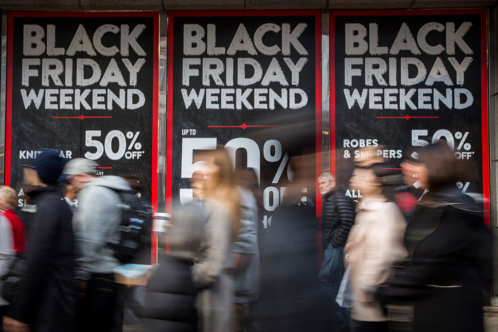 people rushing past Black Friday signs