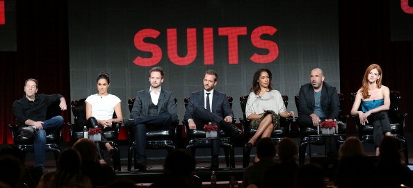 the cast of suits under a sign in red