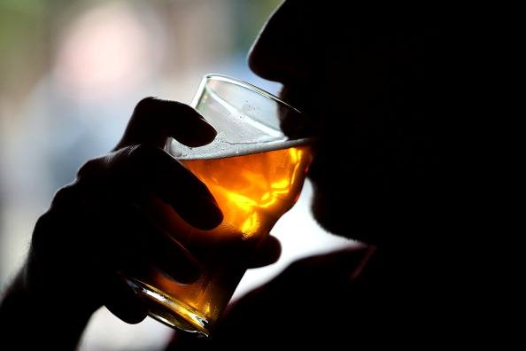 a silhouette of a man drinking a beer