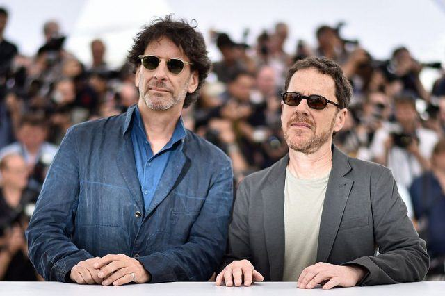Joel and Ethan Coen stand in front of the paparazzi during an event.