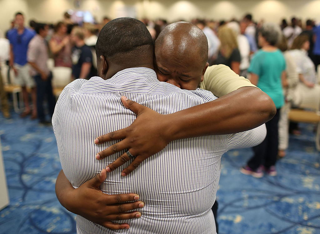 two men embrace with a crowd behind them