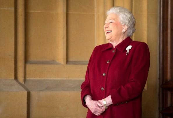 queen elizabeth in a burgundy suit laughing