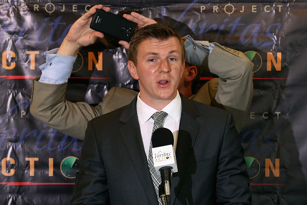 james o'keefe speaking to reporters in a dark suit