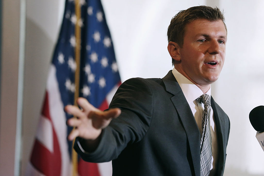 james o'keefe gestures in a suit in front of an american flag