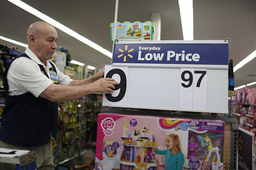 a wal-mart employee adjusts a sign ahead of Black Friday