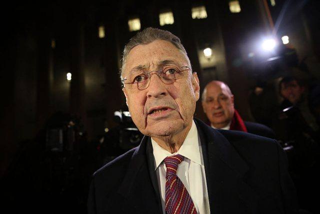 Sheldon Silver surrounded by photographers at night.