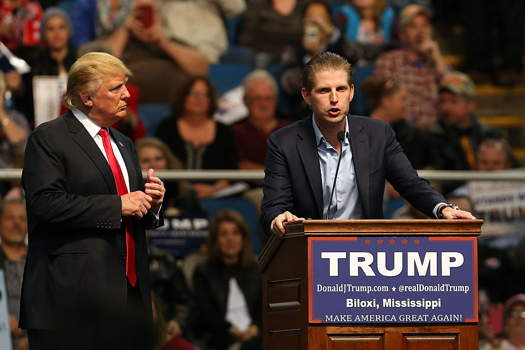 Donald Trump watches his son Eric give a speech at a podium.