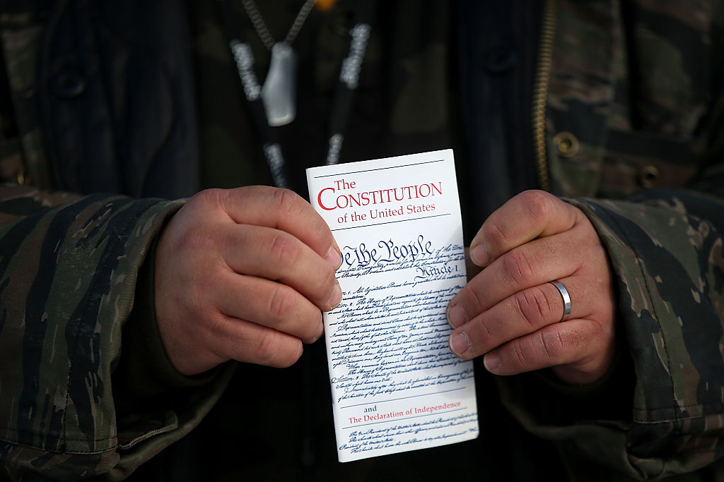 Hands of a normal sized person holds a small copy of the U.S. constitution.