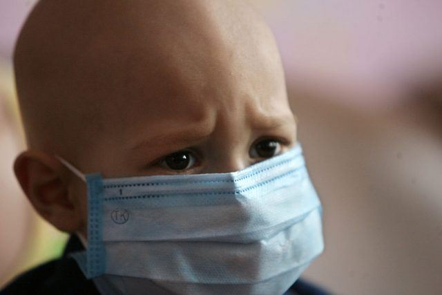 A child with cancer and a mask over his mouth and nose.