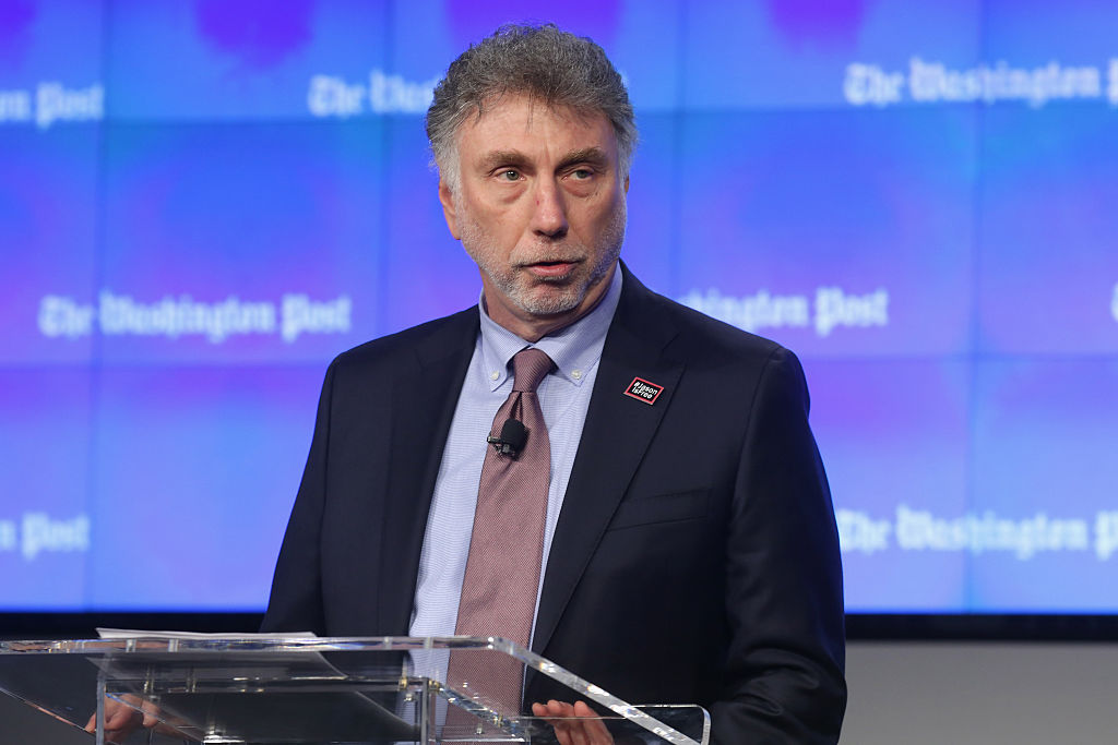 martin baron in a suit and tie in front of a blue background