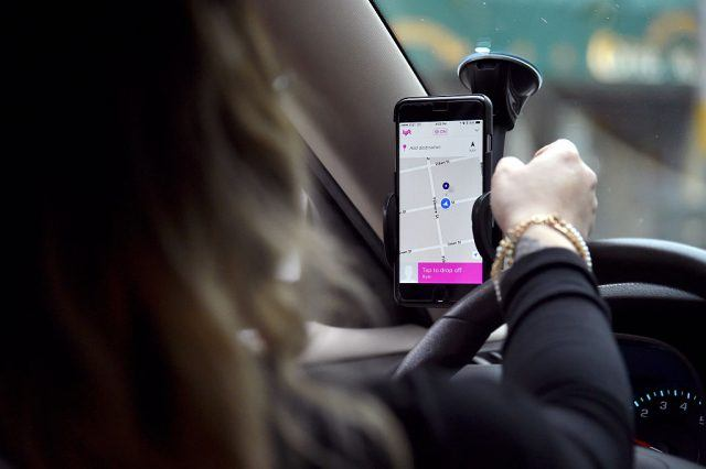 A Lyft driver operates a hands-free device holding a phone displaying a map in the drivers side of a vehicle.