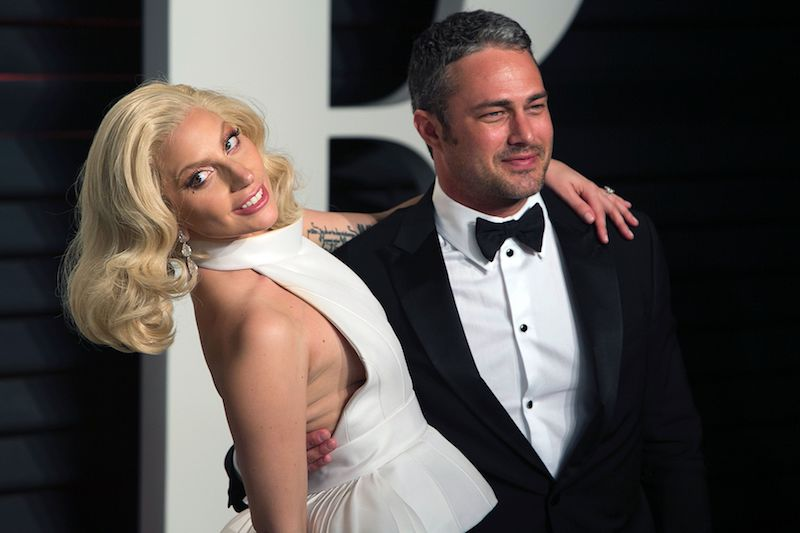 US singer Lady Gaga and her partner US actor Taylor Kinney pose as they arrive to the 2016 Vanity Fair Oscar Party