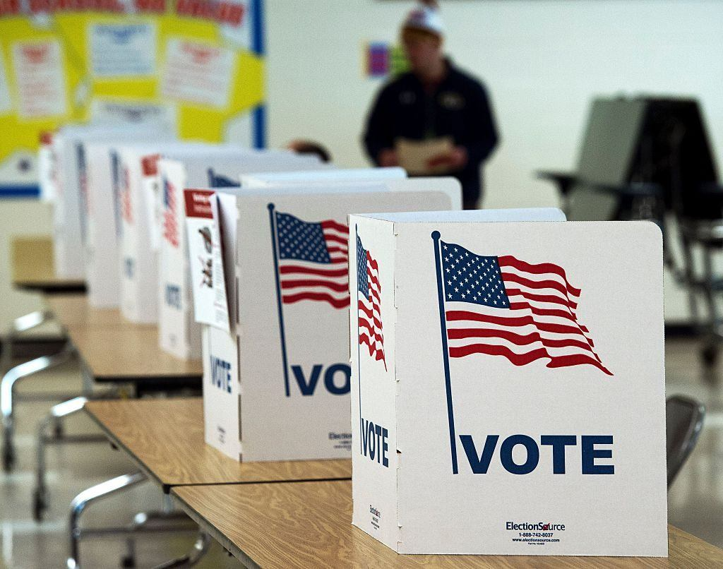 a line of white voting booths with American flags on them