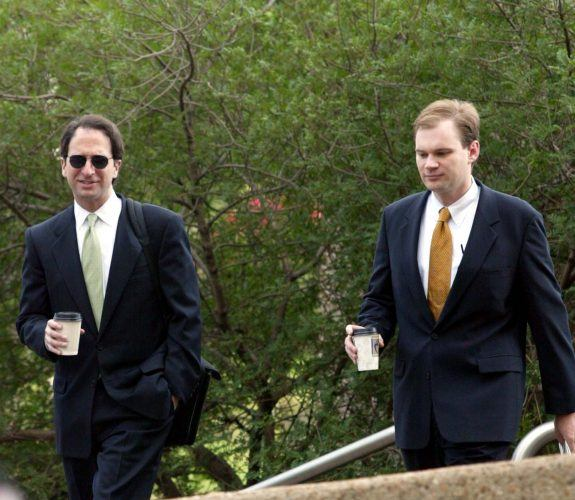 Two white men walking through a courtyard in suits, ties and white shirts.