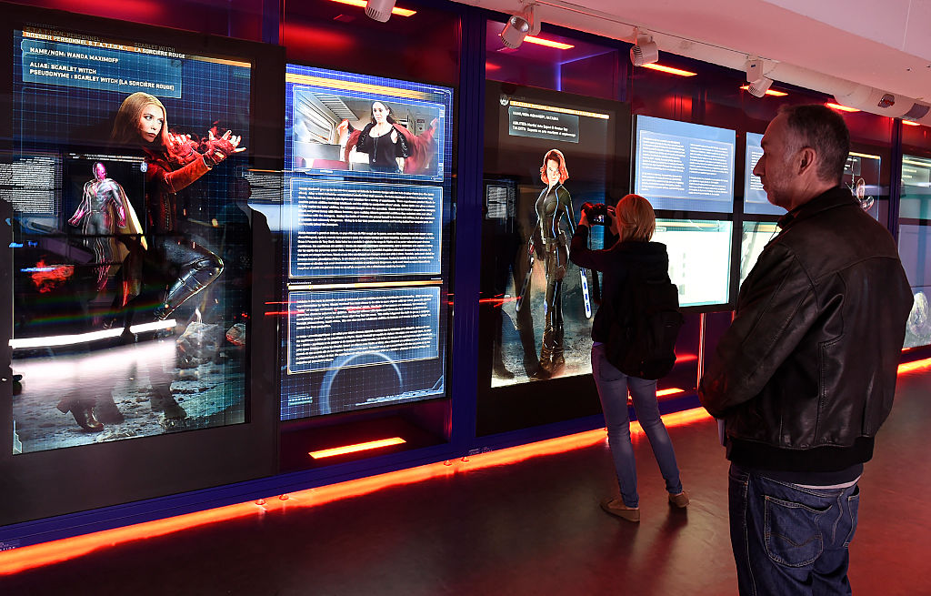 visitors look at an exhibit on scarlet witch and black widow