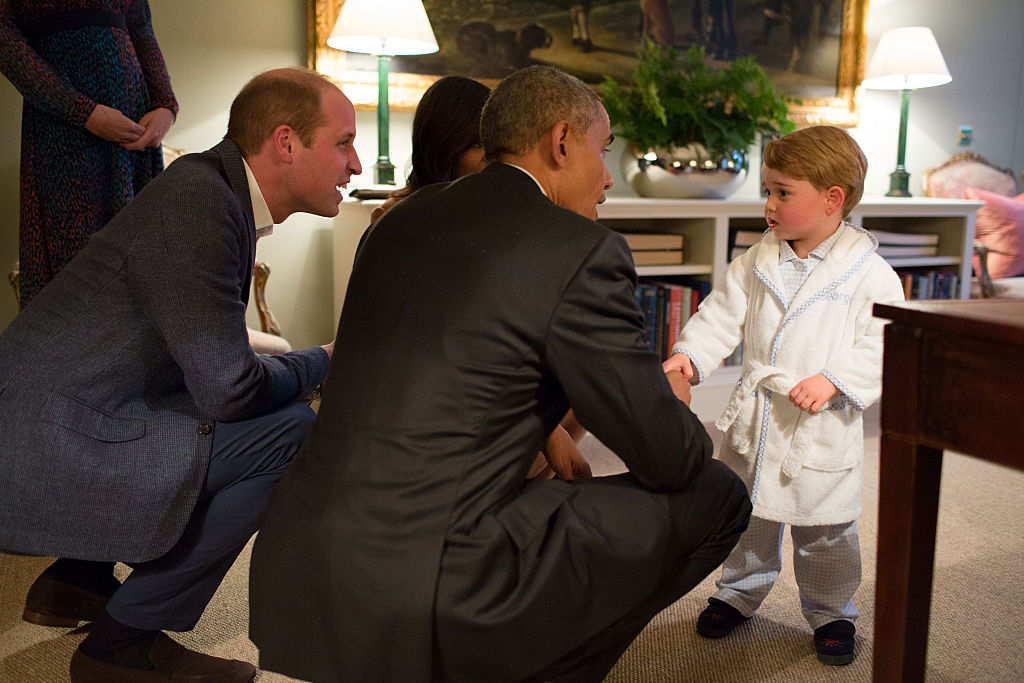 prince george in a white bathrobe meets barack obama in a suit