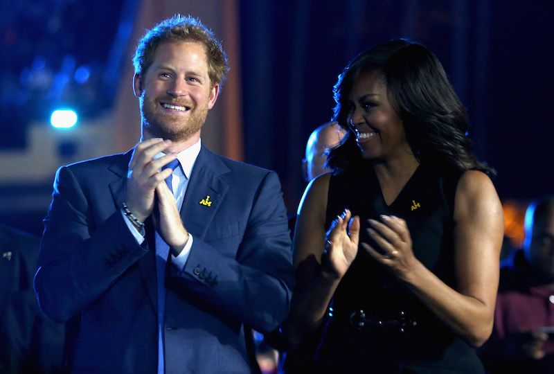 Prince Harry and Michelle Obama stand next to each other and clap their hands