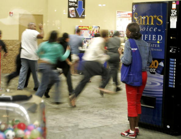 shoppers run past Black Friday signs