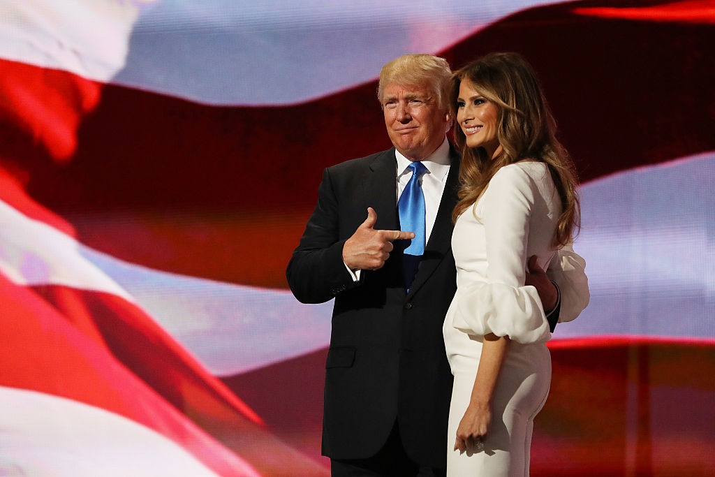 donald trump pointing to melania with an american flag behind them