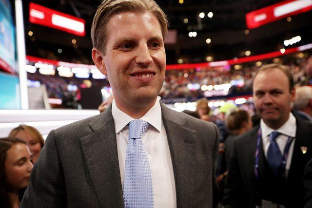 Eric Trump smiling and wearing a gray suit and blue tie.