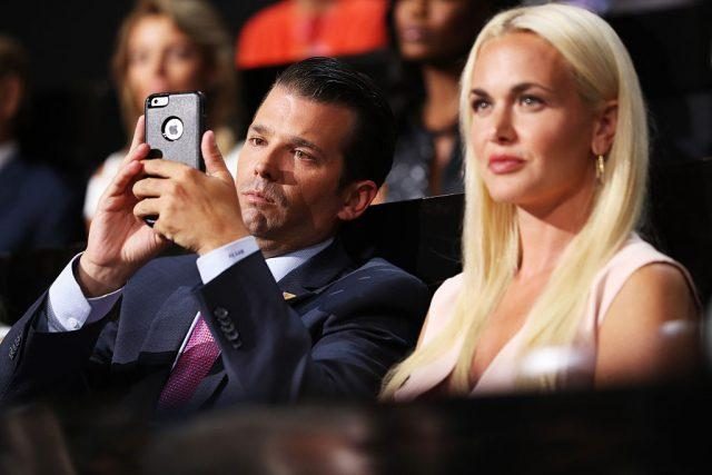 Donald Trump Jr looking at his phone as his wife looks upwards.
