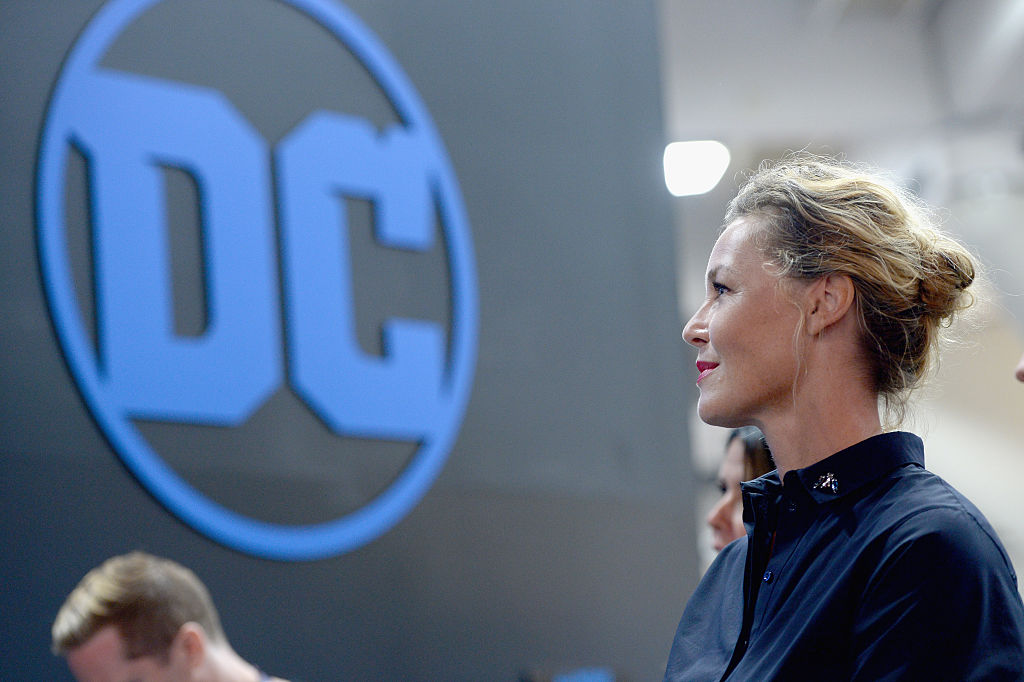 a woman looks at a DC logo