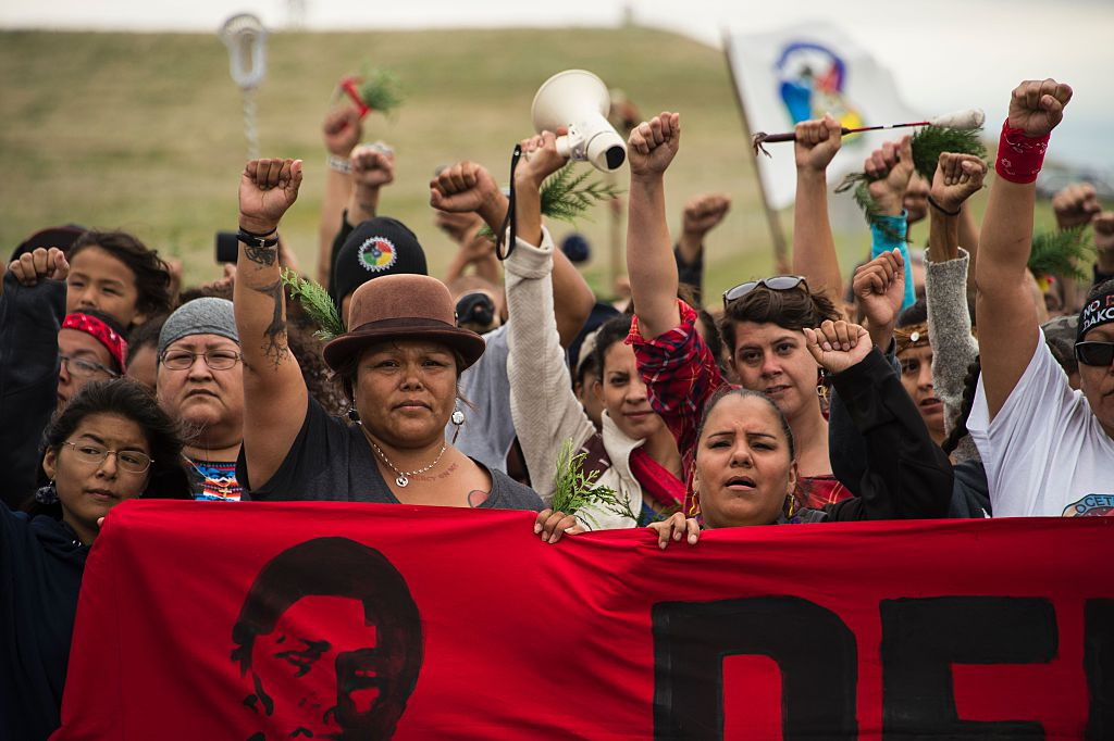 protesters at standing rock march together behind a red banner