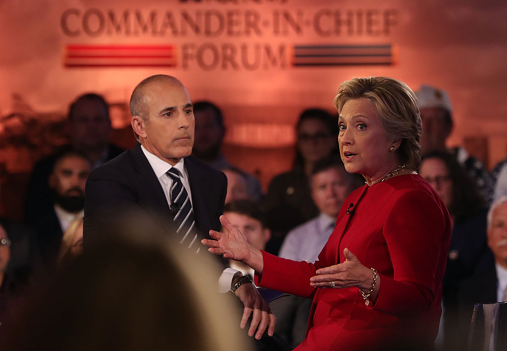 Matt Lauer in a dark suit with Hillary Clinton in red