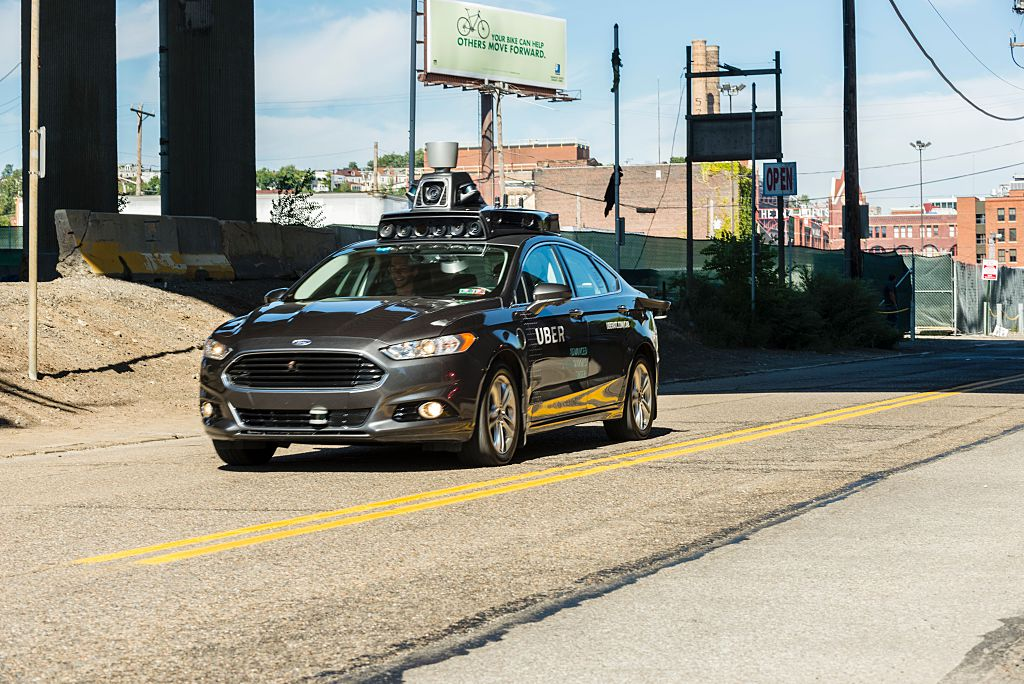 A passenger look on as he rides in a pilot model of an Uber self-driving car