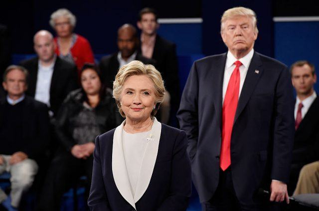 Trump stands behind Clinton during the third presidential debate with people behind him.