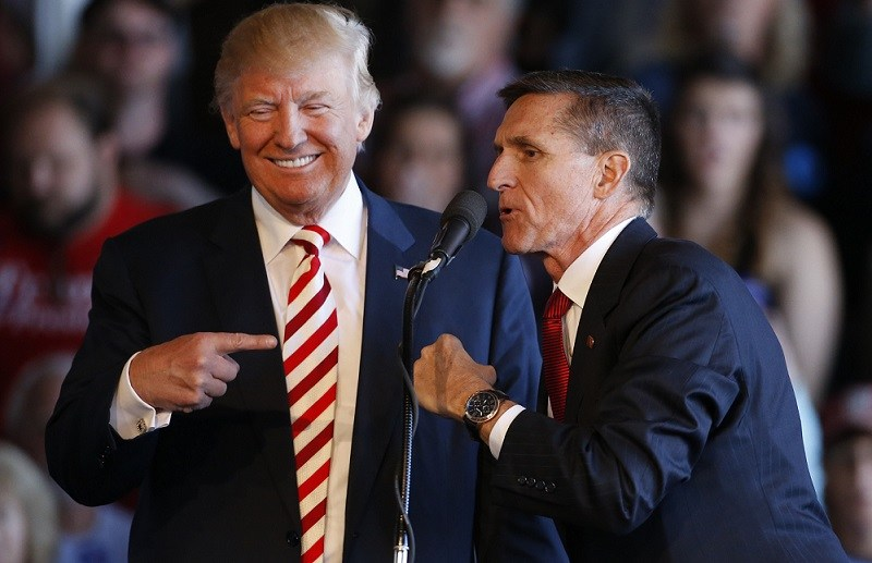 Republican presidential candidate Donald Trump (L) jokes with retired Gen. Michael Flynn as they speak at a rally at Grand Junction Regional Airport on October 18, 2016 in Grand Junction Colorado.