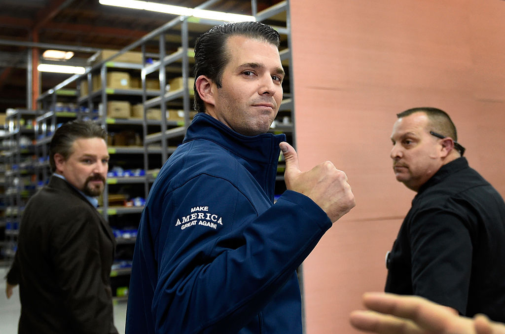 donald trump jr in a blue jacket giving the thumbs up sign