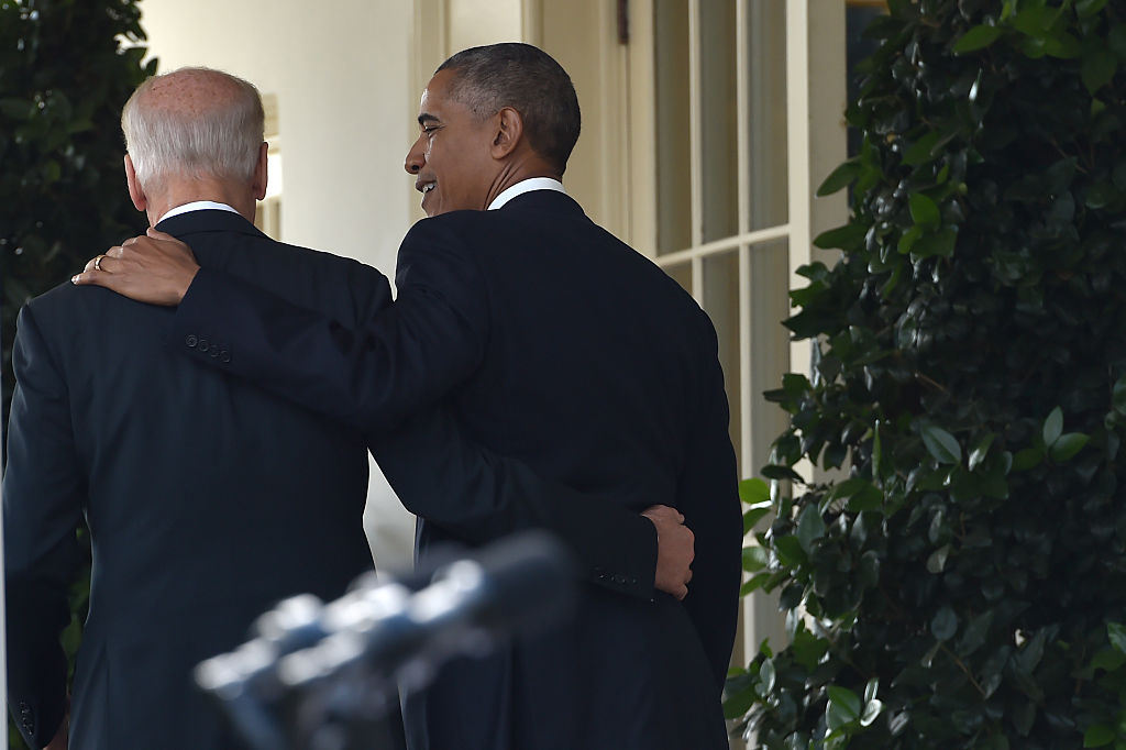 barack obama and joe biden walk in the white house, arm in arm, from behind