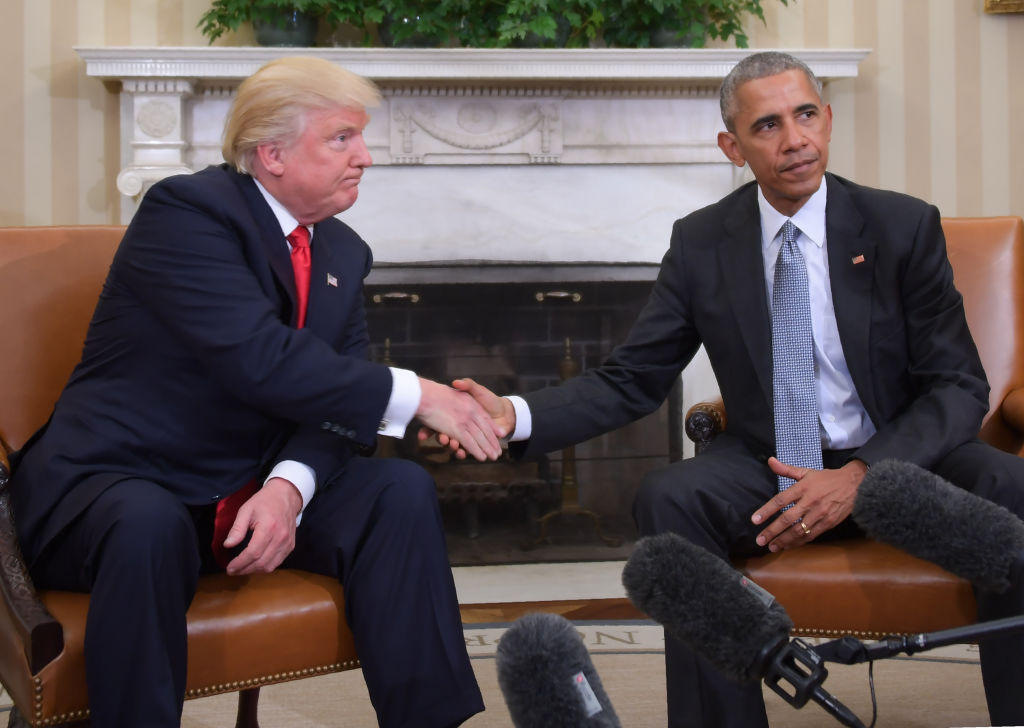 Trump and Obama shake hands.