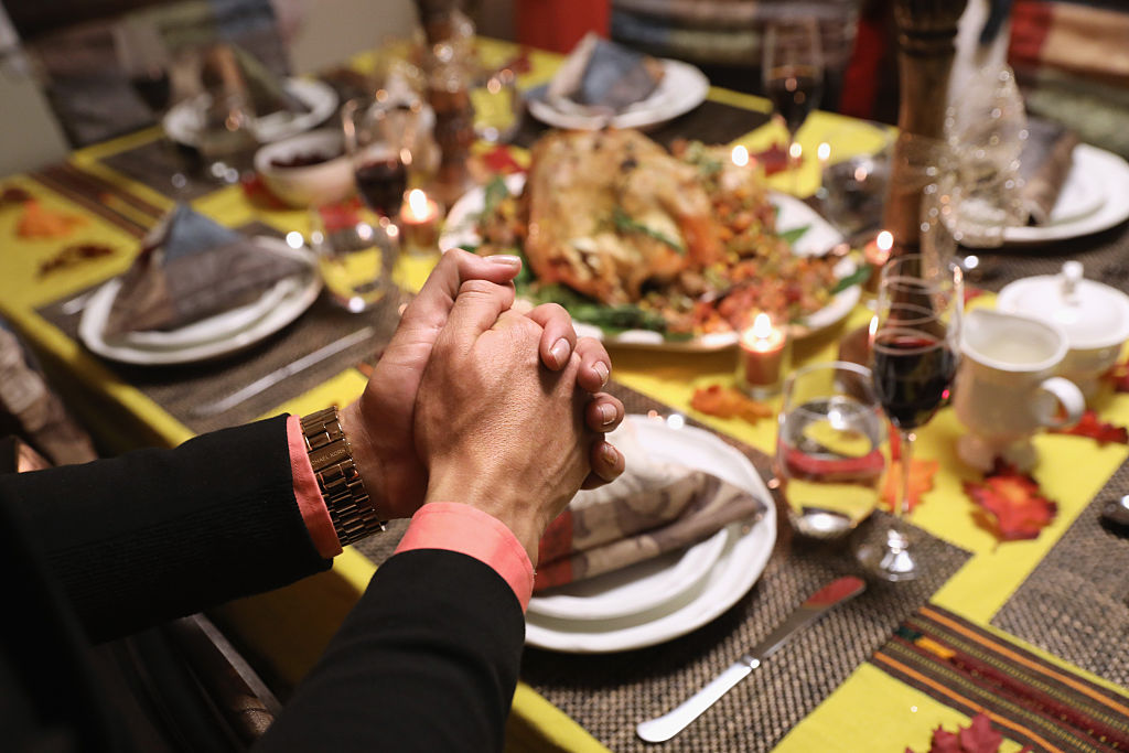 Central American immigrants and their families pray before Thanksgiving dinner