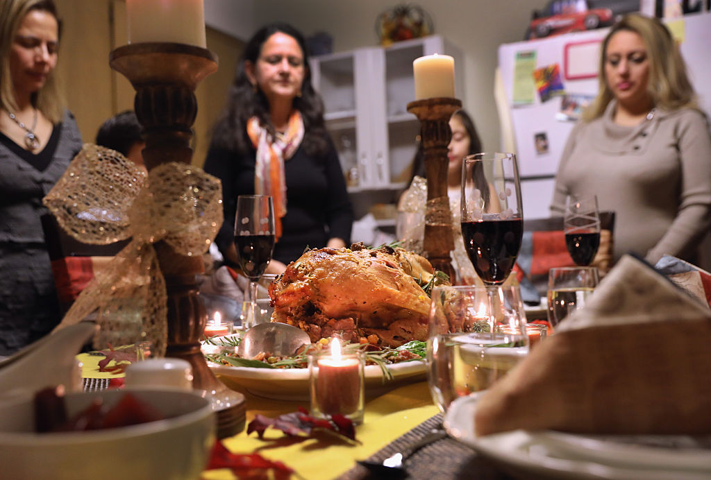 a thanksgiving turkey and settings with a woman and candles