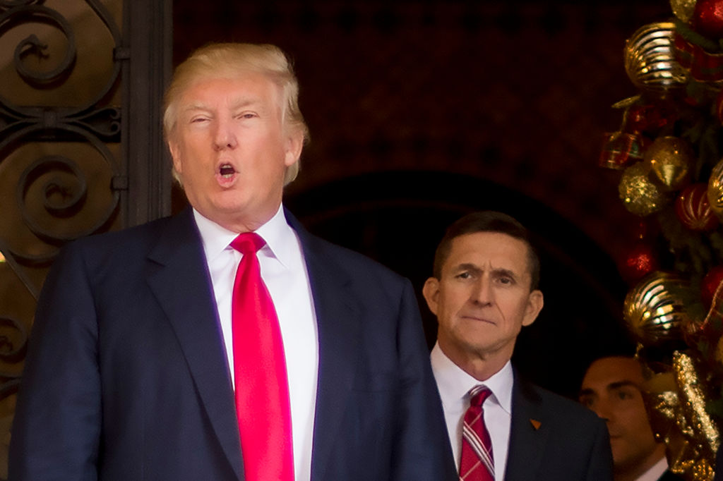 trtump in a red tie with michael flynn, also in a red tie, behind him