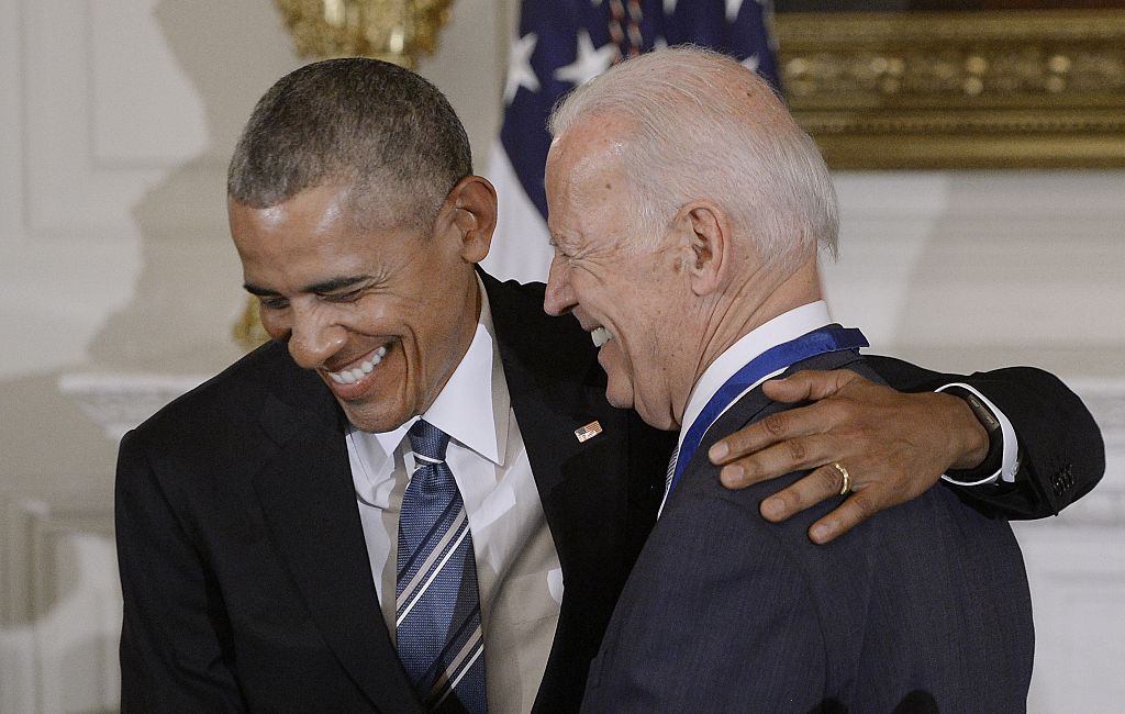 Barack Obama and Joe Biden share a laugh, both in suits