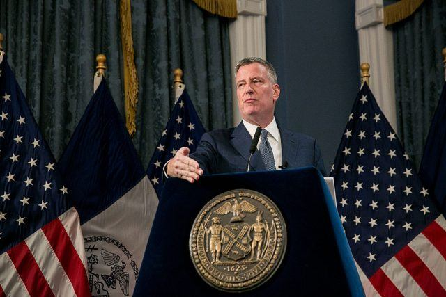 Bill de Blasio stands in front of a podium with the seal of New York City on the front.