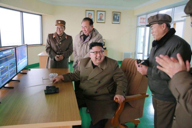 Kim Jing Un sits at a table surrounded by his staff members.