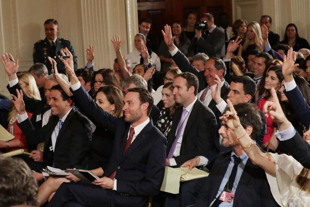 Reporters raise their hands to ask questions at a Trump press conference.