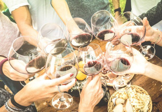 Friends hands toasting red wine glass and having fun outdoors cheering with winetasting - Young people enjoying harvest time together at farmhouse vineyard countryside - Youth and friendship concept