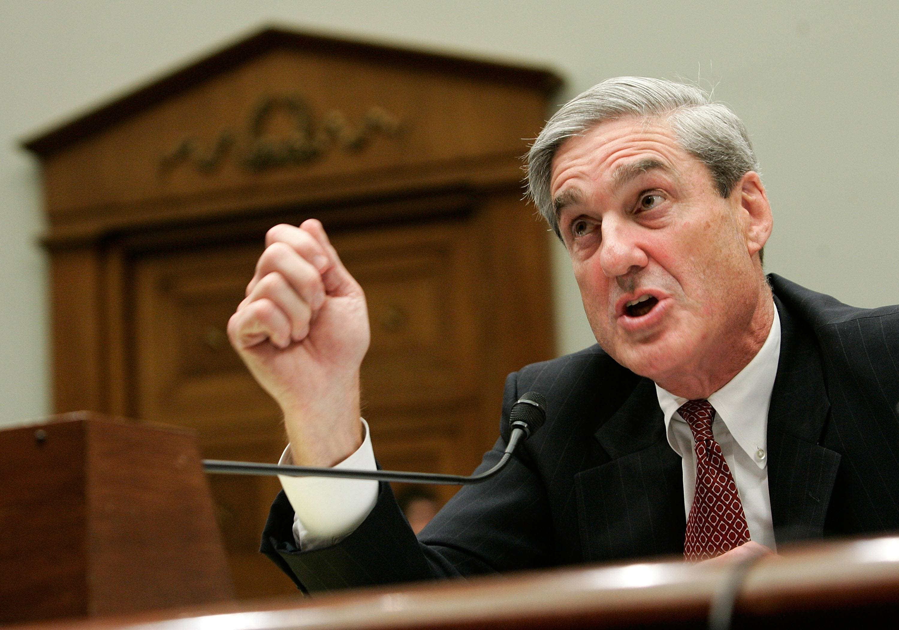Mueller in a black suit screaming into a microphone.