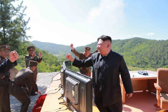 Kim Jong Un stands in celebration with a bunch of his generals in front of monitors on top of a mountain on a sunny day.
