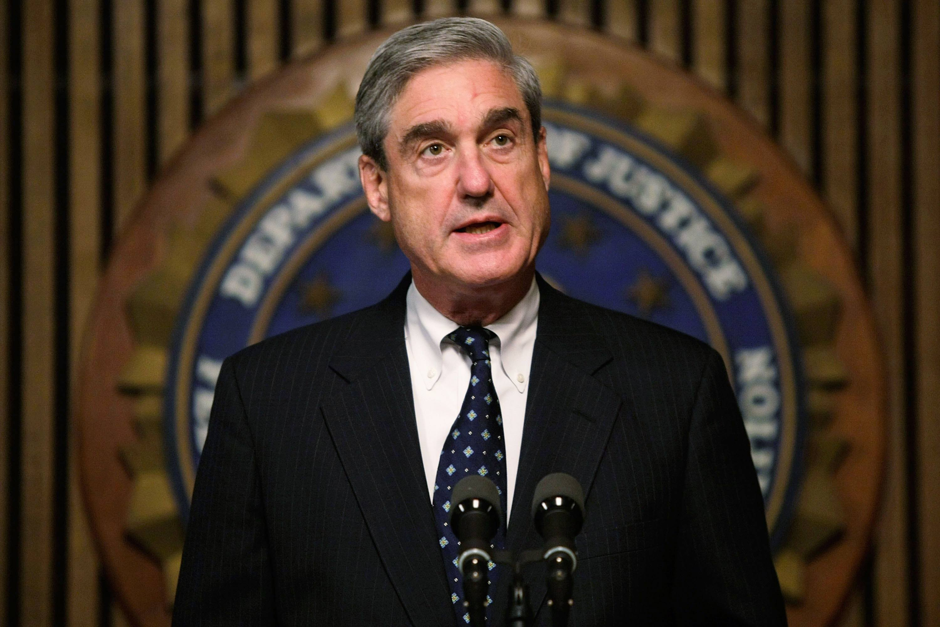 Mueller standing in front of the seal of The DOJ.