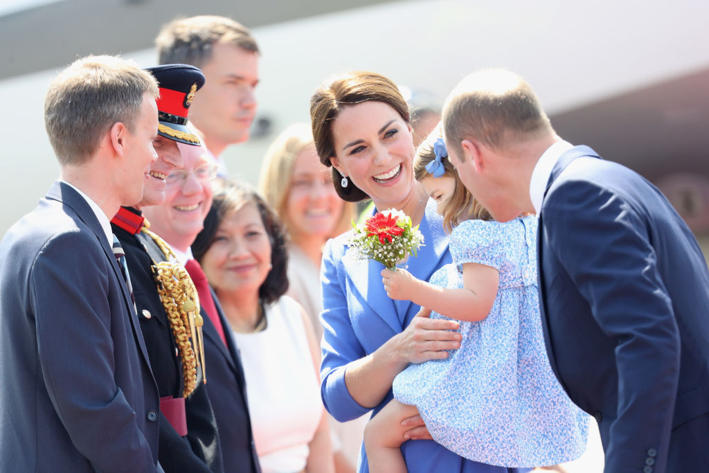 kate middleton and her daughter charlotte surrounded by officials
