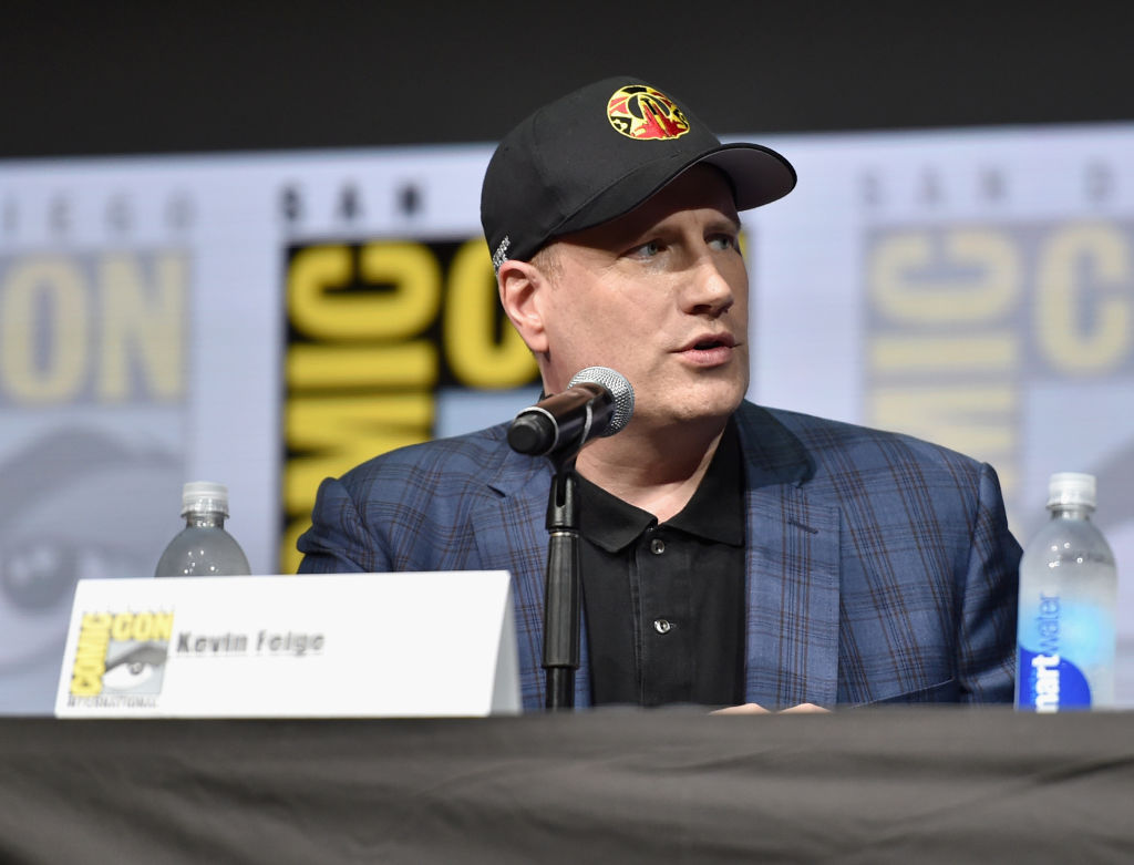 Kevin Feige in a cap and blue jacket speaking into a microphone at Comic-Con.