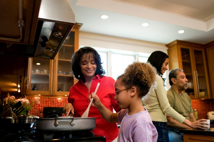 Grandmother cooking with granddaughter, rest of family talks in background