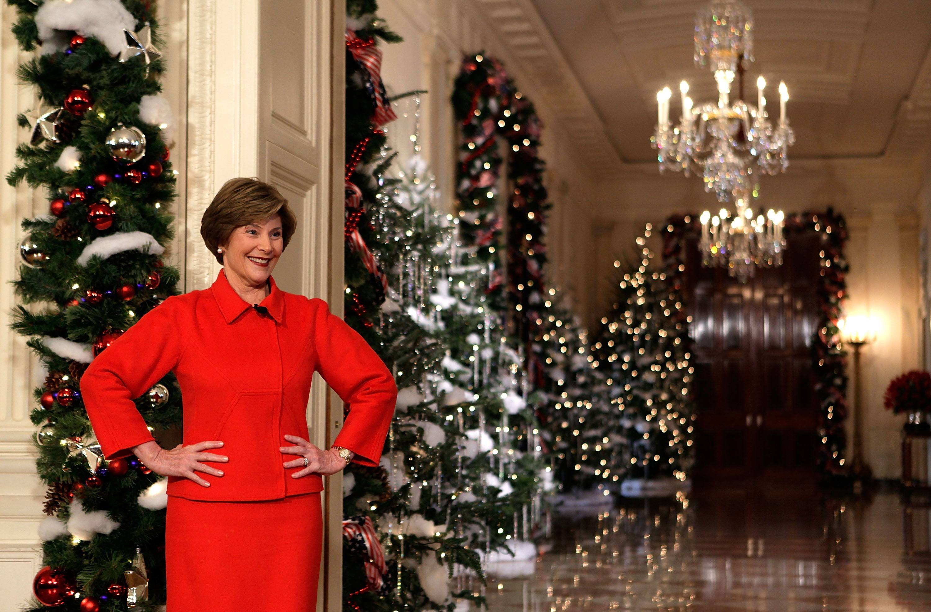 Laura Bush standing in front of Christmas decorations
